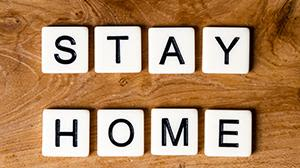 Scrabble letters spelling out Stay Home on a wooden background.