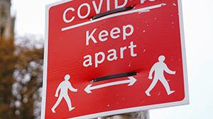 A red sign with the words - COVID-19, keep apart