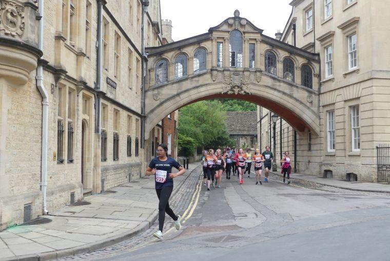 Runner going under and past bridge between buildings