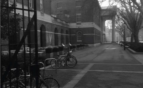 Black & white photo of bikes parked outside a large building