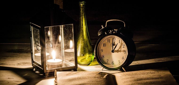 Clock, lantern, bottle and book on table