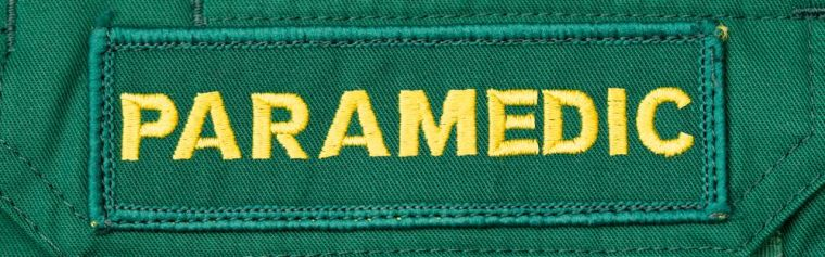 """A woven badge that says """"paramedic"""" on a uniform."""