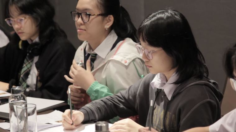 Screenshot of the video 'Three-minute thesis competition' showing students taking notes during the competition
