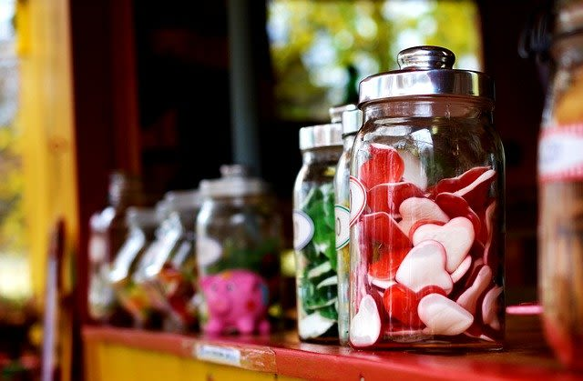 Jars of sweets, with red, heart-shaped candies in the foreground
