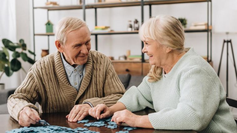 Two elderly people having fun doing a jigsaw together