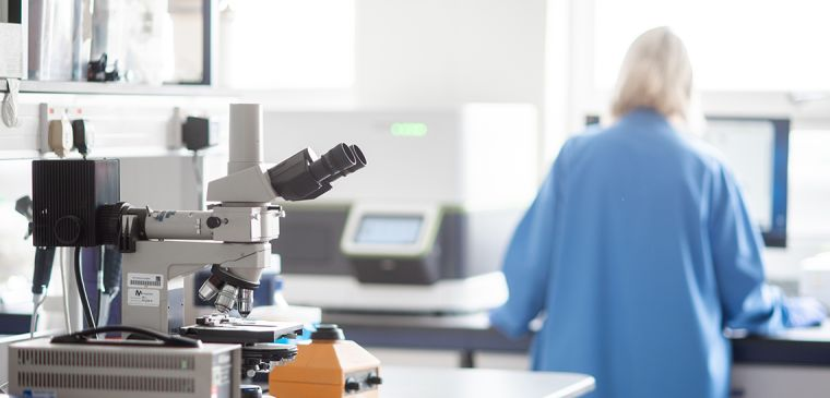Female researcher in lab with microscope in foreground