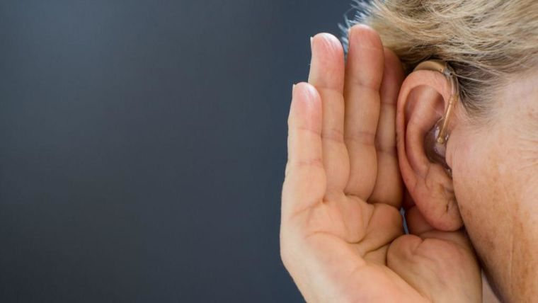 Elderly woman with hearing aid on grey background. Close up.