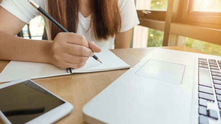 Person writing on paper with laptop on table