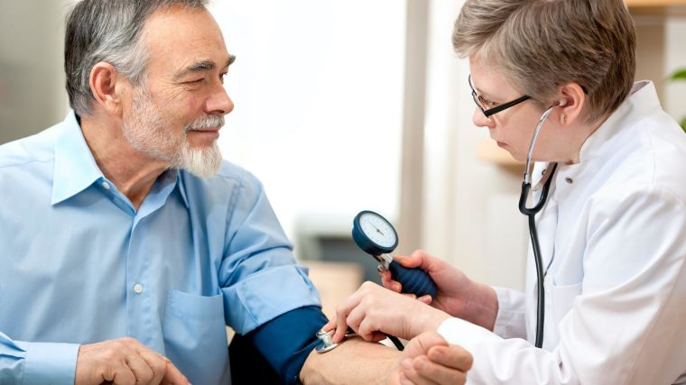 A female doctor does a blood pressure test on an elderly patient