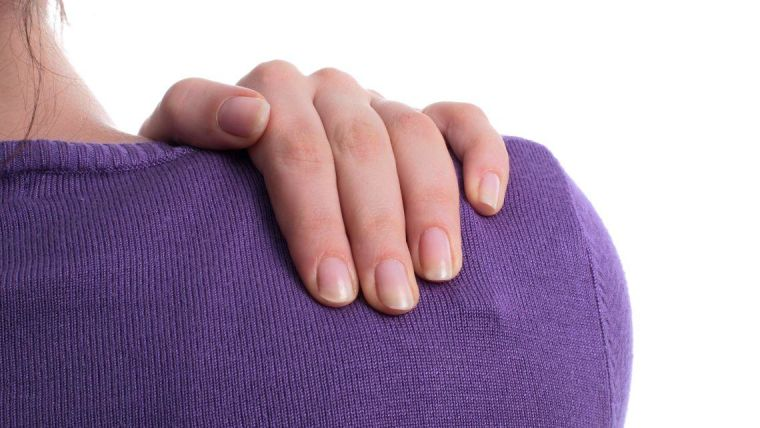 Woman grasping her shoulder