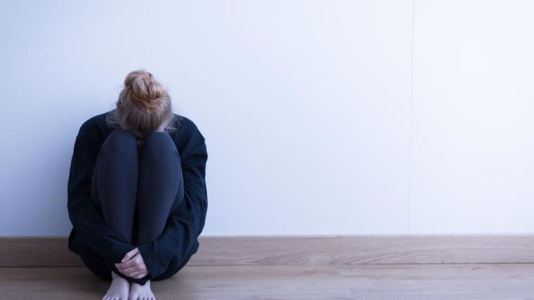 Woman sitting curled up on the ground