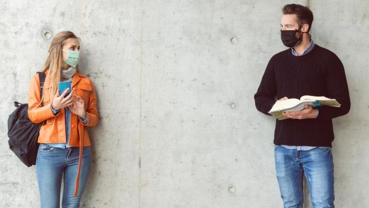 Male and female students wearing facemasks standing at a distance