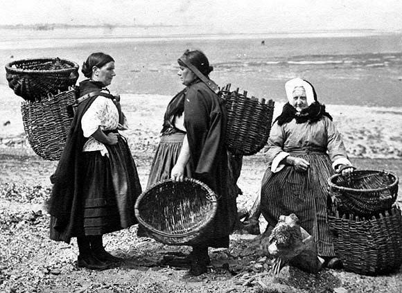 Three female cockle-pickers with baskets, at the coast