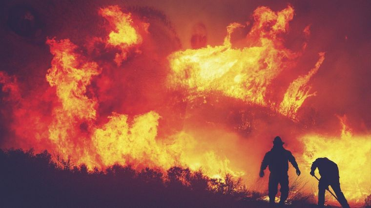 Two firefighters silhouetted against a wildfire