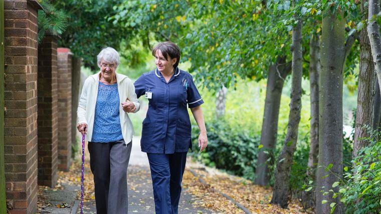 Care home worker walking with elderly person.