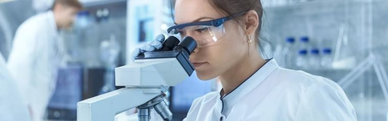 Medical Research Scientists Looking at Samples Under Microscope. She Works in a Bright Modern Laboratory