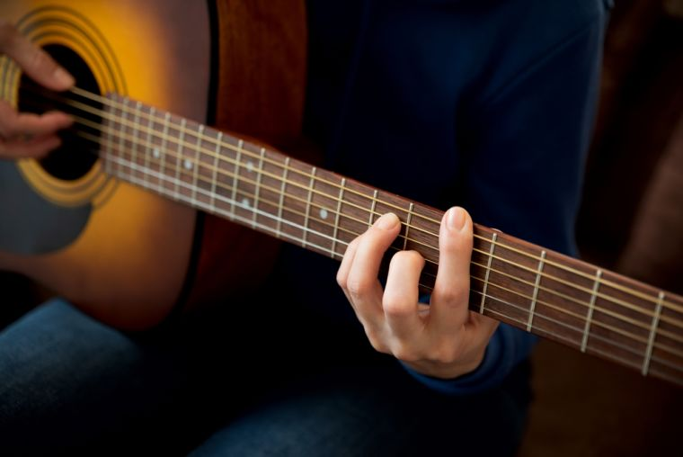 Close-up woman playing acoustic guitar.