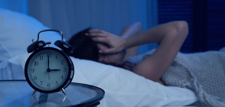 An alarm clock showing 3AM next to a sleeping woman who seems unable to sleep