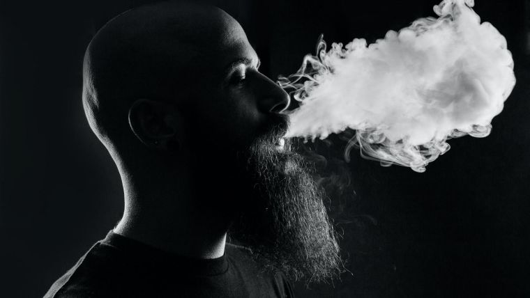 A man exhaling smoke from a vape