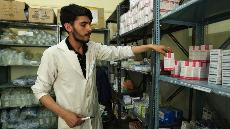 Health worker sorting prescriptions on shelves