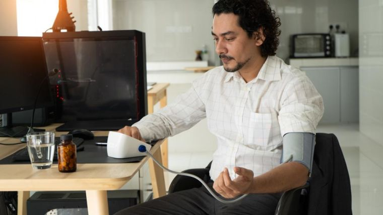 A man taking his blood pressure at home.