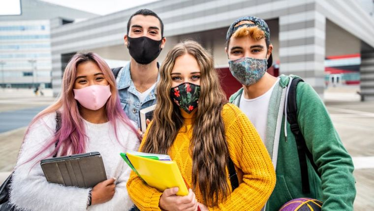 4 young people wearing face masks with school books/bags standing together