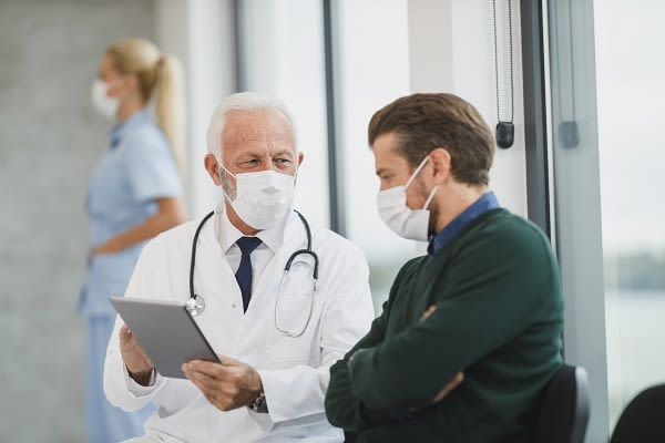 Doctor showing patient clipboard (both are in masks).