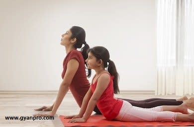 mother-daughter-practicing-yoga-home-260nw-652026601