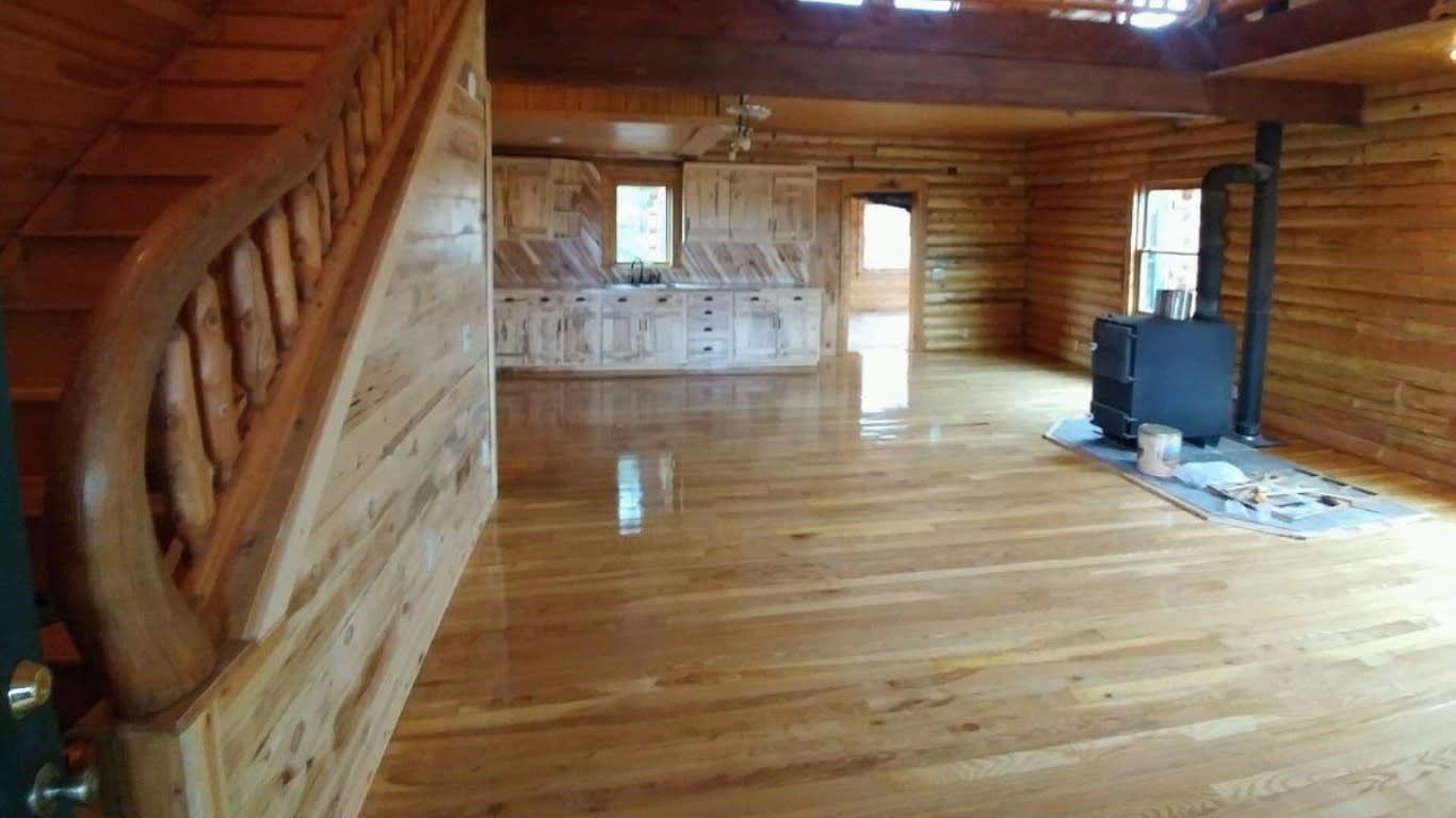 Image showing a lightly stained floor in a large room with wooden walls and staircase, all the same stain
