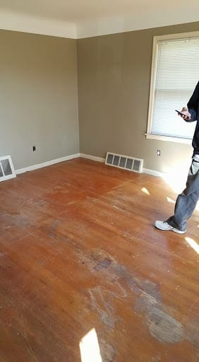 Image showing a room with damaged, discolored hardwood, with a Wilson's employee's lower body in the right side of the image