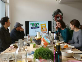 People round the table watching a presentation from a guest