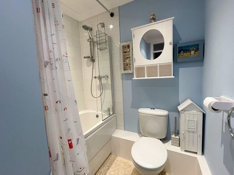 Bathroom with a small bath and overhead shower