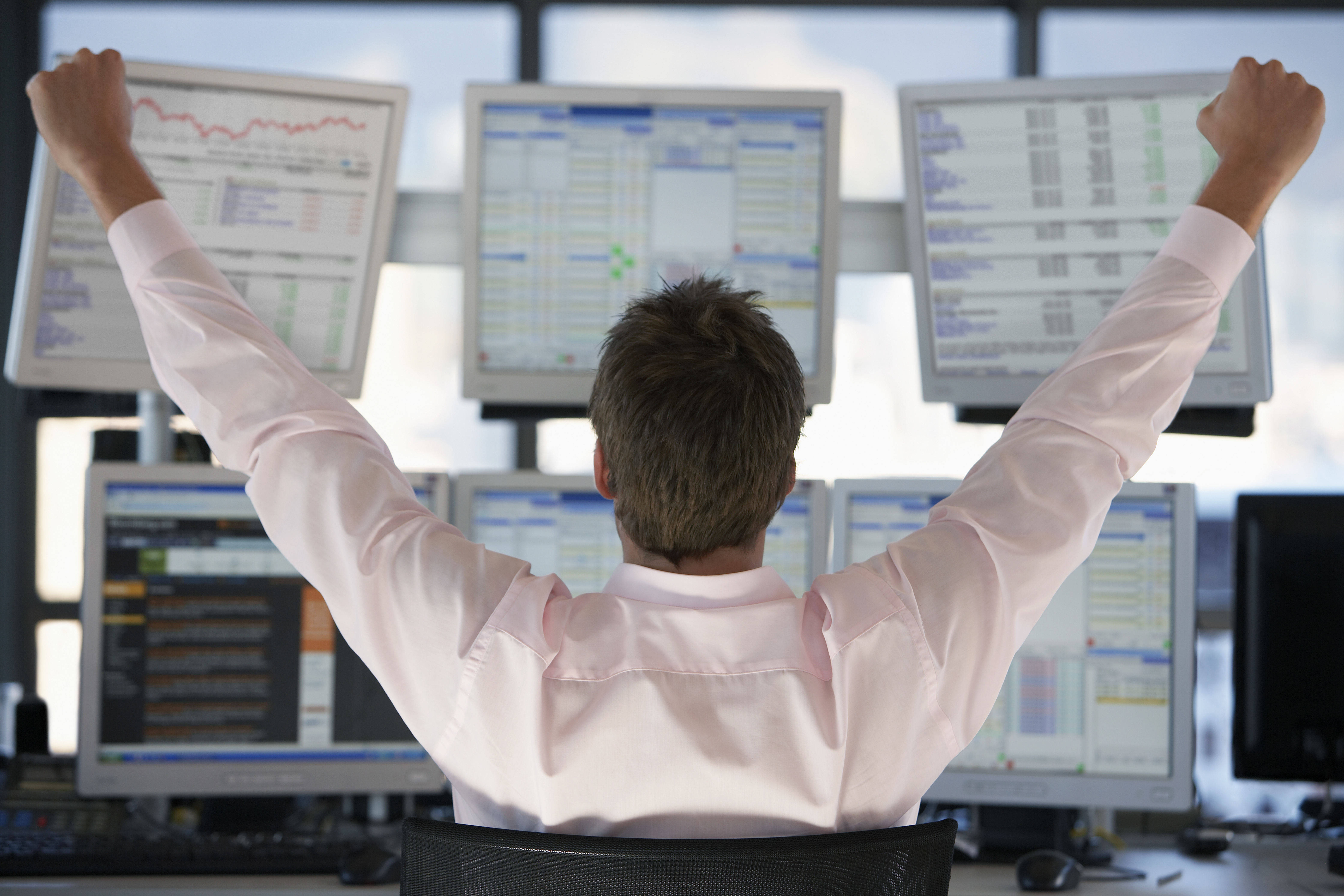 Happy Hedge Fund Trader looking at screens