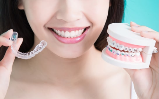 woman holding out a clear aligner and a dental model with braces