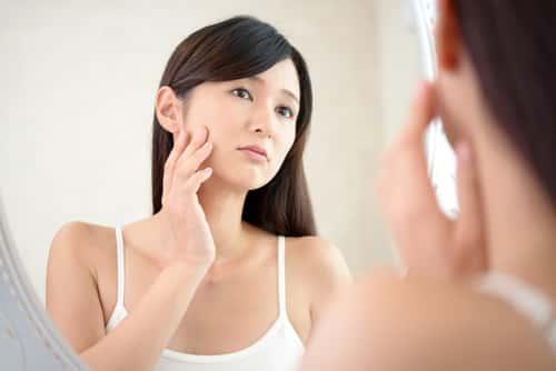 Woman examining her face
