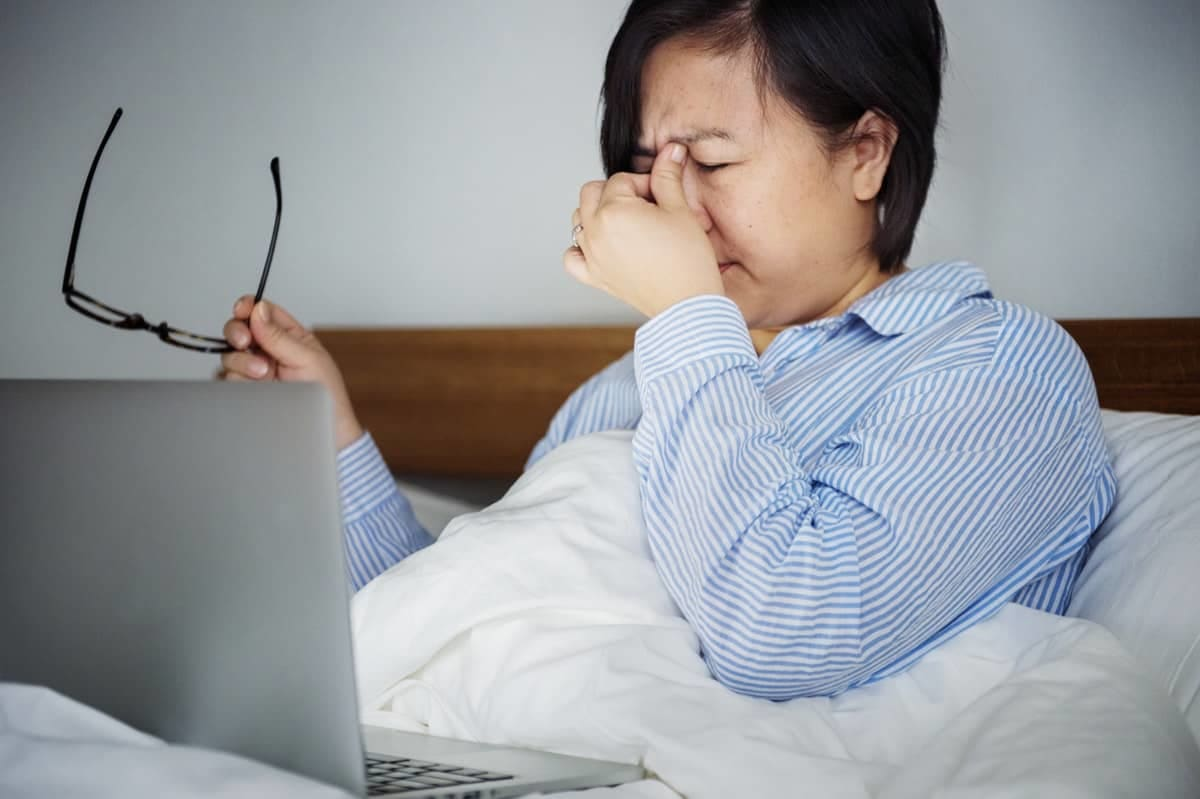 woman rubbing her eyes in bed