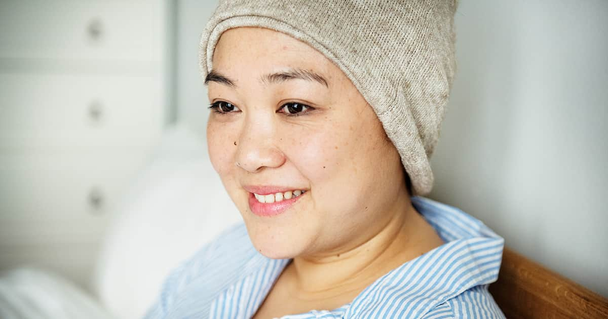 a smiling woman with a knitted cap