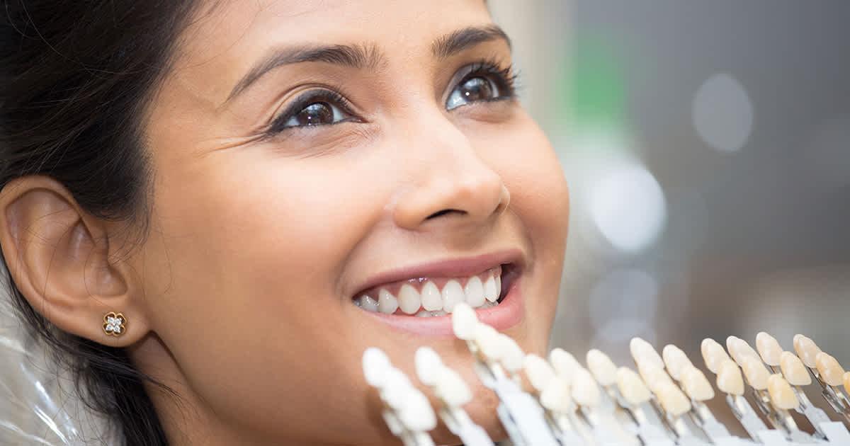 woman smiling as she gets fitted for veneers