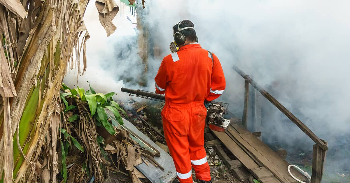a man fogging a residential area to kill mosquitoes