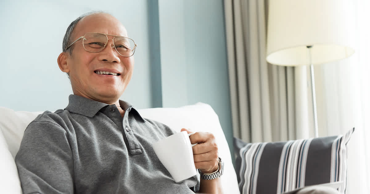 old man with glasses in living room