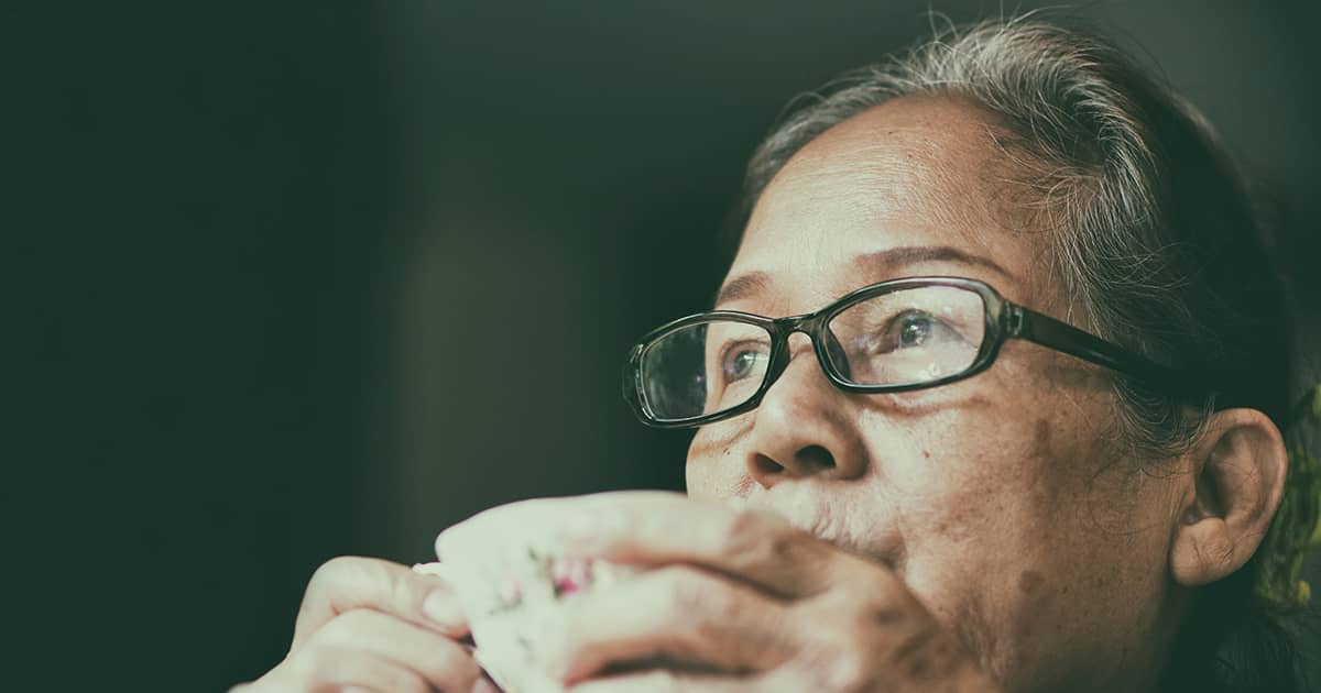 old woman with glasses drinking tea