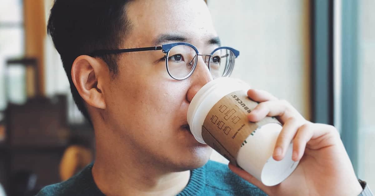 an asian man drinking starbucks coffee