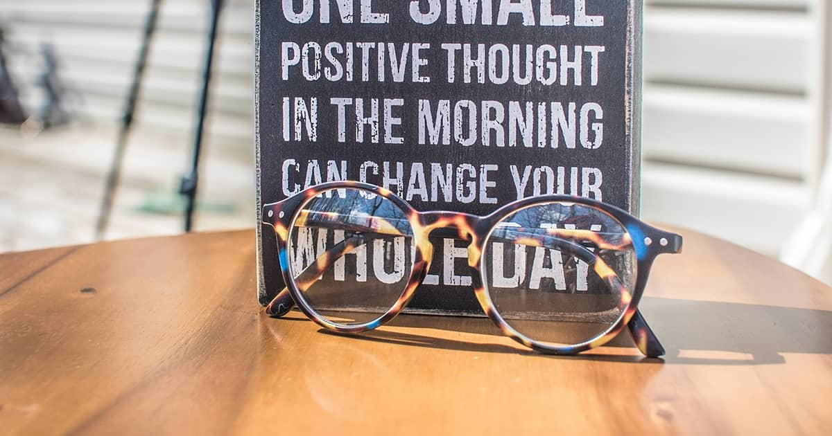 a wooden table with glasses and an inspirational sign