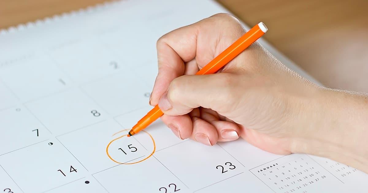 a woman circling date on a calendar