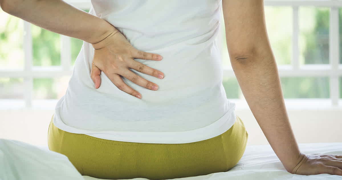 a woman sitting on a bed with back pain