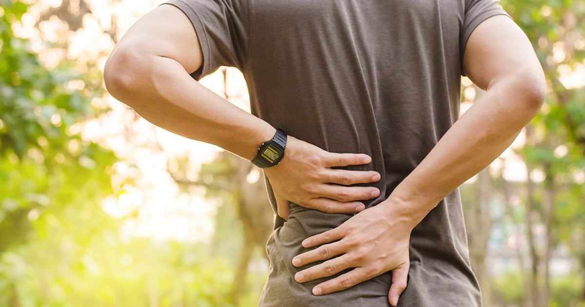 a man outdoors with a backache