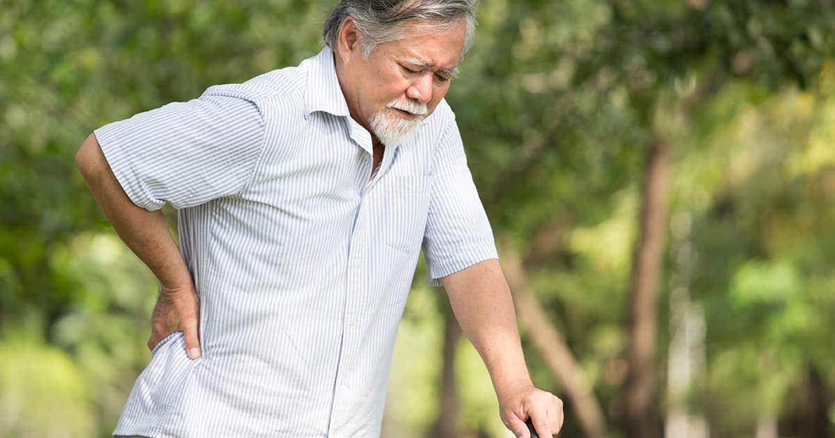 elderly gentleman walking in park with back pain