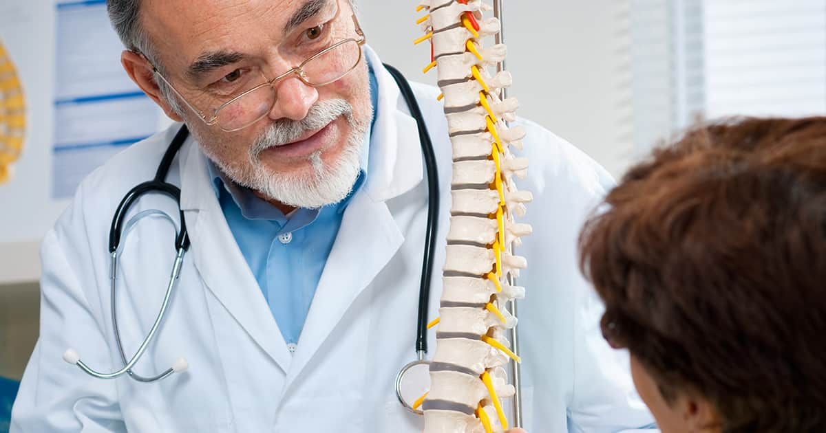 doctor explaining a spine model to a patient
