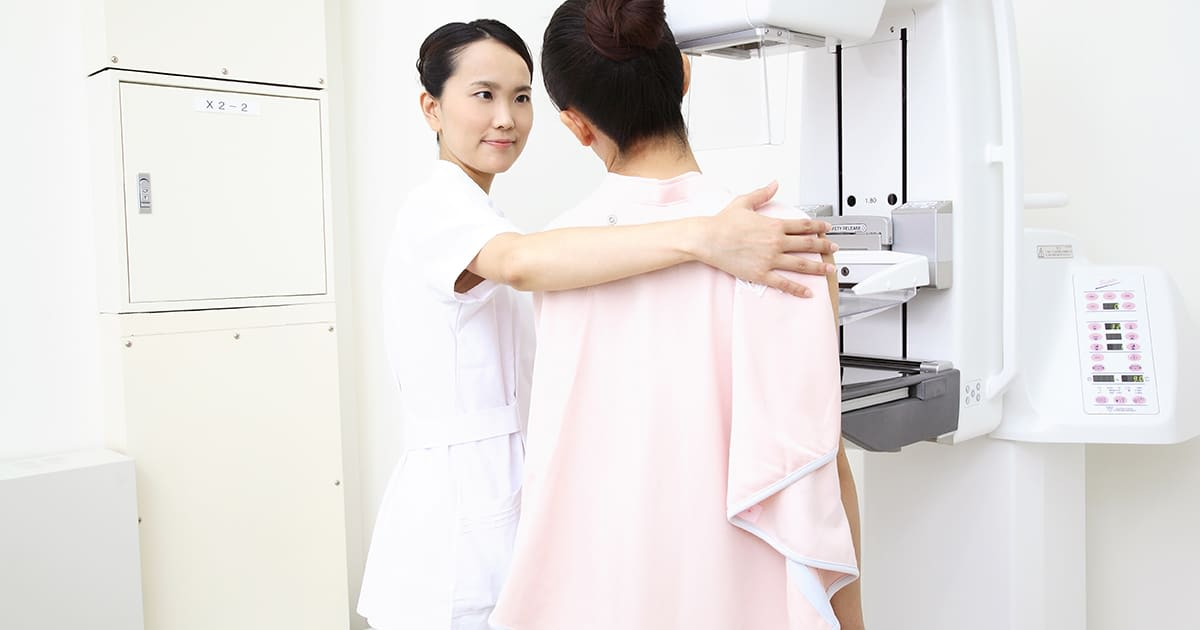 woman preparing with a nurse for a breast scan