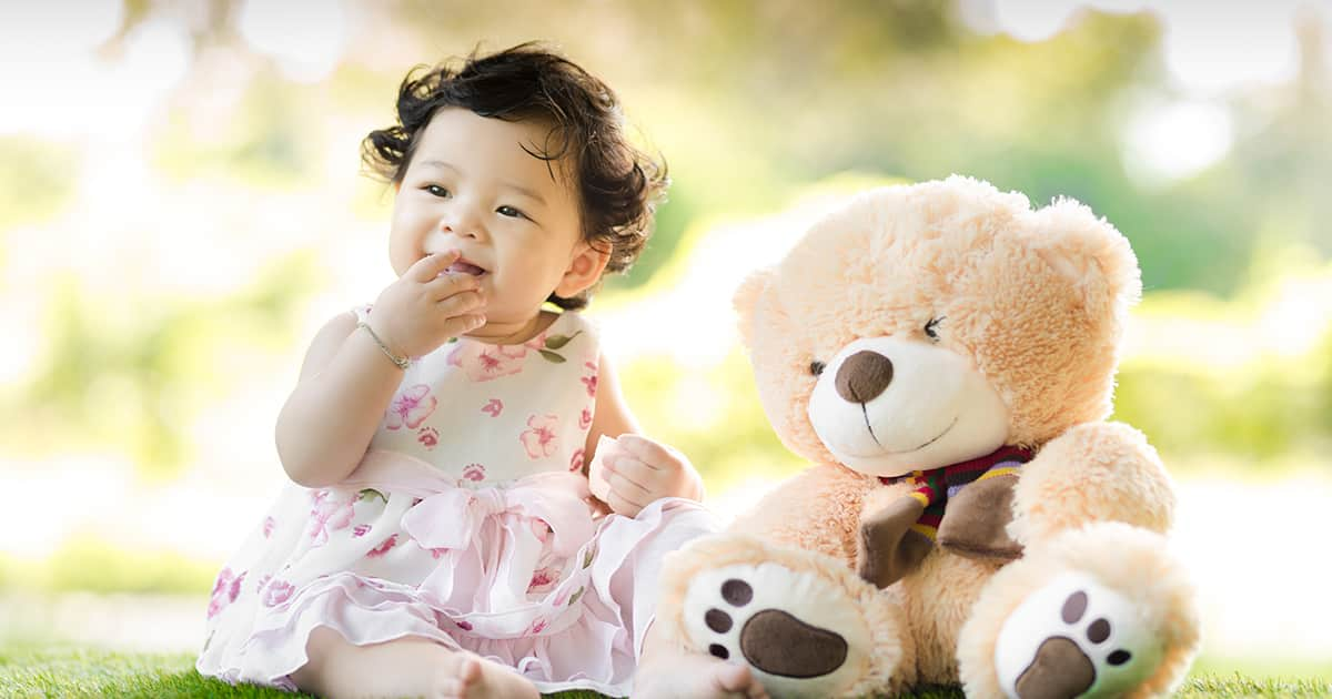 a happy baby with a teddy bear on grass